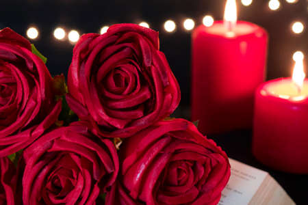Beautiful red rose with romance candle lights on bokeh light background. Valentine's day and wedding concept. Banco de Imagens