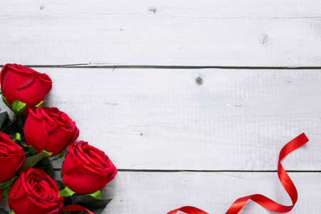 Top view of beautiful red rose and ribbon on white wooden background with copyspace for valentine and love theme.