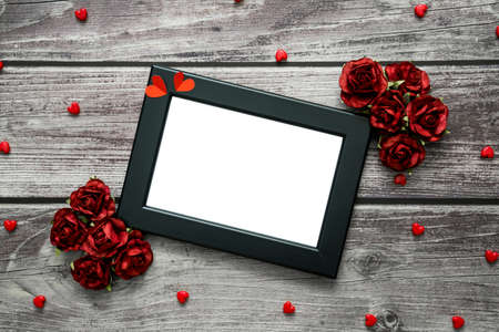Black frame with hearts and roses on vintage wood background with copyspace for text. Top view for valentine theme.