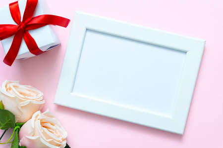 Valentine frame with sweet rose and gift box on pink background with copyspace for text.