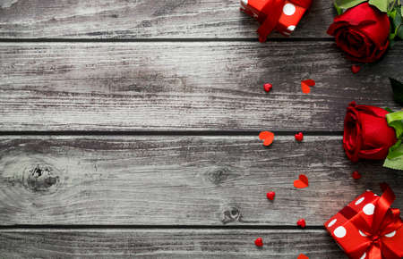 Red rose, gift box and heart on wooden background with copy space for text. Top view valentine day concept.
