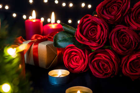 Red roses bouquet with romantic candles and gift box against bokeh lights for valentine day concept.