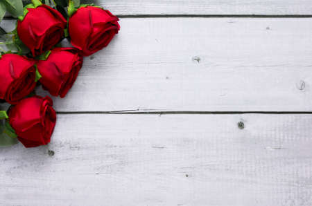 Red roses on white wood background with copy space for text for Valentine and wedding frame concept. Banco de Imagens