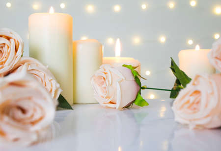 Wedding and Valentine day background with beige roses and candles against bokeh light, sweet and clean concept. Banco de Imagens