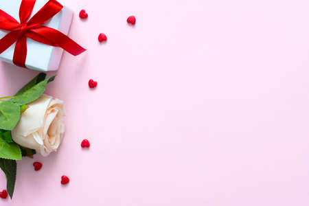 Rose, gift box and heart on pink background with copyspace for text. Top view of valentine's day or love frame concept.