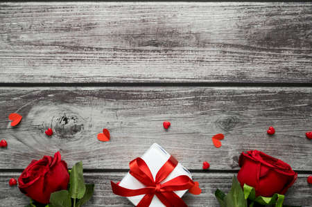 Valentine day background with roses, heart and gift box on wooden table with copy space. View from above