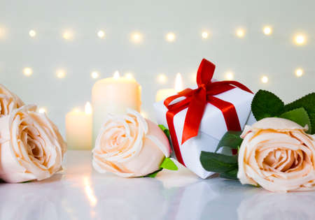 Love Valentine day theme with beige rose, gift box and candle on white background in bokeh light. Фото со стока