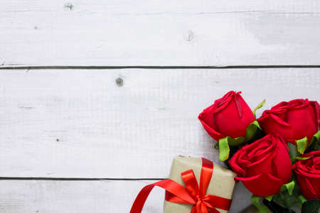 Valentine day greeting card with red rose flowers and craft gift box on white wood with copyspace for text.