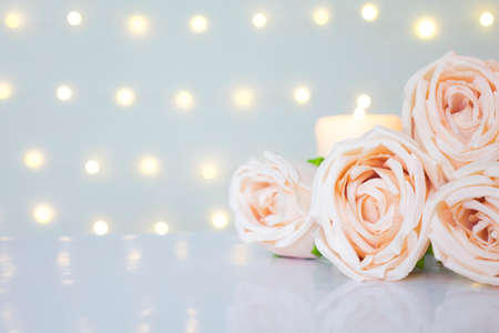 Roses on white against glow bokeh lights background with copyspace. Clean valentine day, romantic love concept.