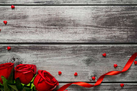 Love valentine day concept. Red rose, heart and ribbon on dark wood table with copyspace. Top view