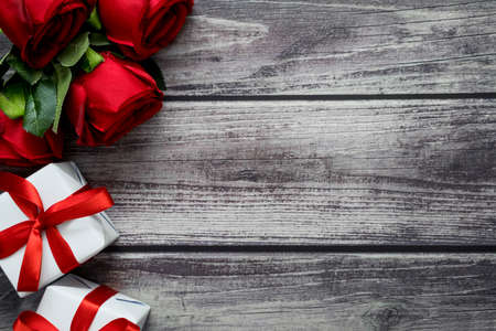 Top view rose and gift box on vintage wood background with copyspace for love or valentine day theme. Banco de Imagens