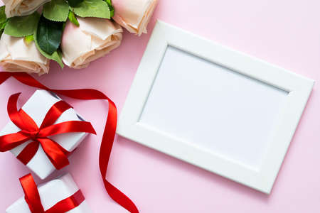 Top view of white frame with copy space , roses and gift boxes on pink background. Sweet Valentine or romance love theme.