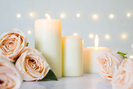 Beige rose bouquet and white candles on white with bokeh lights background. Concept of clean valentine's day, wedding or love. Фото со стока