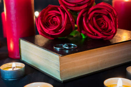 Wedding ring on book with roses and candles for love, wedding and valentine feelings.