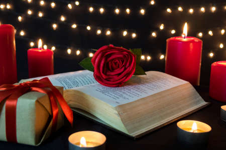 Romantic red rose on open book with gift box and candles in bokeh lights at night.