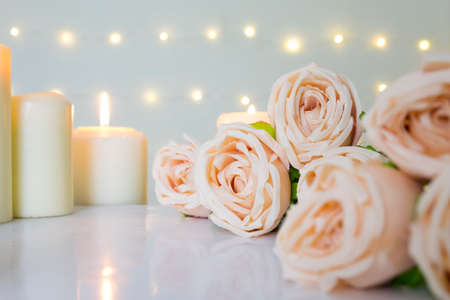 Beige rose bouquet and white candles against bokeh lights background for clean valentine, wedding theme.