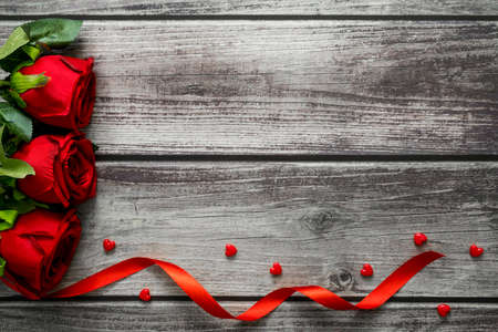 Red rose and heart on wooden background. Top view and copyspace for love, wedding and valentine theme. Фото со стока