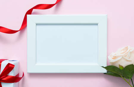 White photo frame, gift box and rose on pink background. Top view and copyspace for love, valentine day concept. Фото со стока