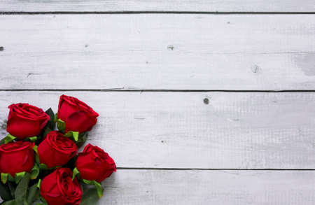Red roses on white wooden desk with copy space.