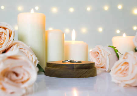 Wedding rings, beige roses and white candles on bokeh light background for feelings love, romance and valentine's day. Фото со стока