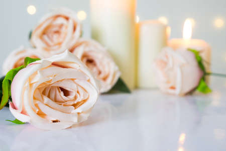 Light pastel roses and white candles on white table with bokeh lights. Valentine's day, love and wedding concept.
