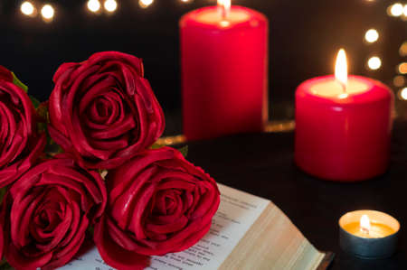 Red rose on book and candles for romantic valentine night.