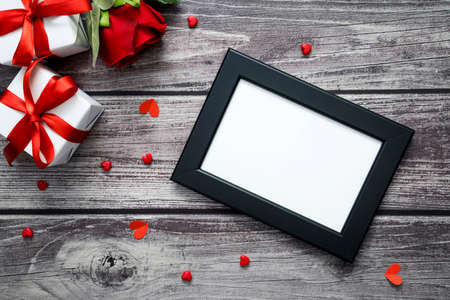 Empty black frame mock up with red rose, gift box and heart on old wood. Top view valentine, wedding and love.
