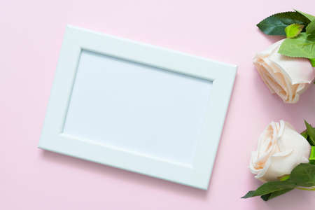 Blank white frame mockup with pastel roses on pink backgroud for love, wedding or valentine day theme. Фото со стока
