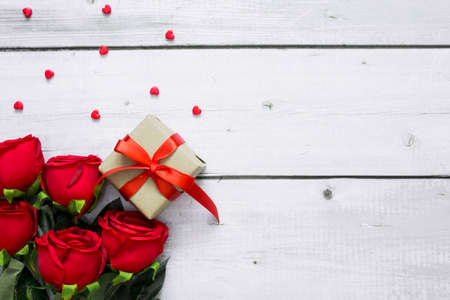 Love or Valentine concept with copy space for text. Red beautiful roses, heart and gift box on white wood background. 스톡 콘텐츠