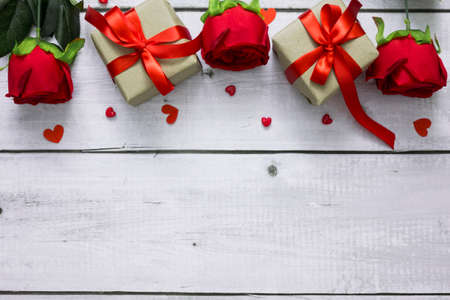 Flat lay for love or valentine concept with gift box, roses, and heart on white wooden with copy space. Banco de Imagens