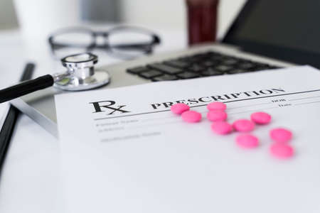 Rx prescription with pink medicine, stethoscope on laptop on doctor table. Фото со стока
