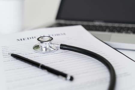 Stethoscope on medical form on doctor desk. Banco de Imagens