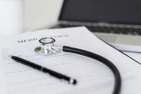 Stethoscope on medical form on doctor desk. 스톡 콘텐츠
