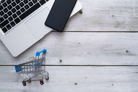Top view of laptop, smartphone and cart on white wood background with copyspace for online shopping concept. Фото со стока