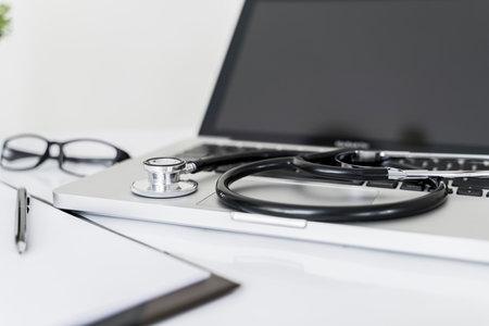 Stethoscope on laptop on doctor desk in office. Фото со стока