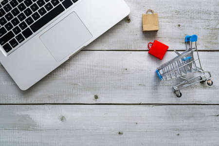 Top view shopping online concept with laptop, paper shopping bags and cart