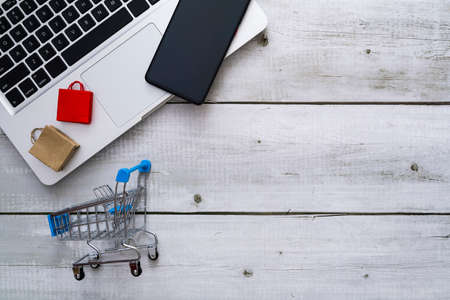 Flat lay for shopping online theme with shopping bag, smartphone on laptop and cart