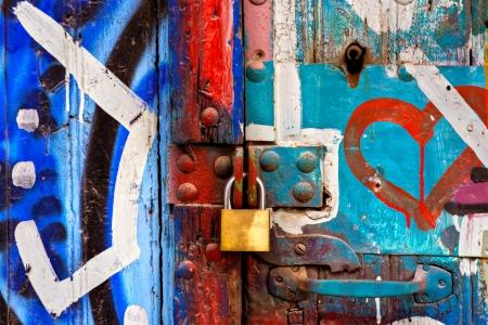 Metal padlock on graffiti door