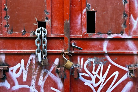 Metal padlocks and chain on metal door Stock Photo - 9340200