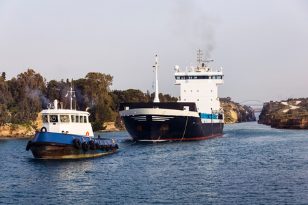 seaway: Cargo ship and tugboat crossing Corinth canal, Greece Stock Photo