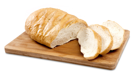 A regular baked french loaf sliced on a wooden cutting board on an isolated white background photo