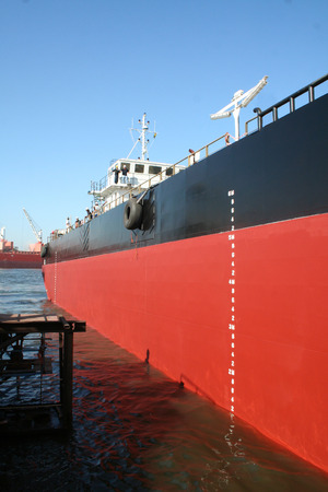 A large red and black tanker ship being renovated in a shipyard Stock Photo - 29027460
