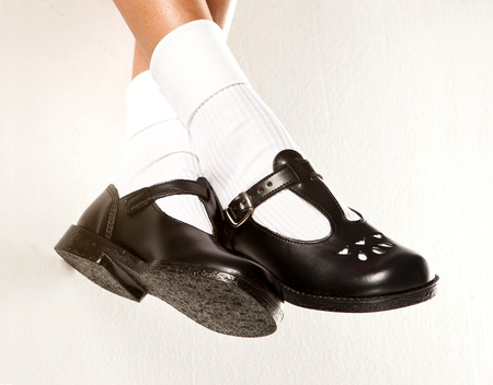 A dangling set of kids legs with short white socks and black girls school shoes on a white background Stock Photo