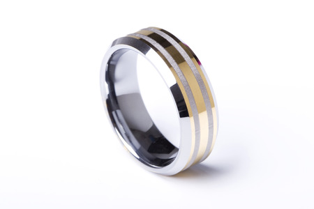A mens plain wedding ring band made out of silver and gold on an isolated white studio background