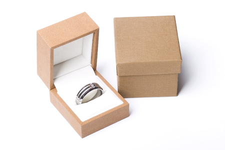 A mens plain wedding ring band made out of silver and gold in a box next to a closed one on an isolated white studio background photo