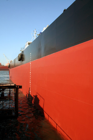 drydock: A large red and black tanker ship being renovated in a shipyard