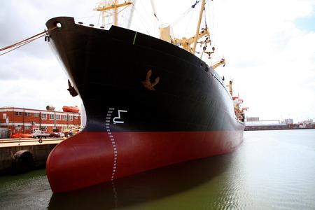 Een grote rode en zwarte tanker schip in een scheepswerf wordt gerenoveerd