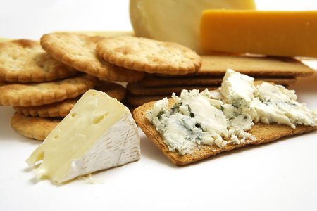 A collection a various types of cheeses and cracker biscuits on an isolated white studio photo