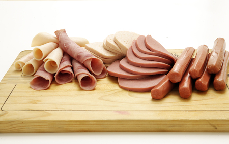 A collection of cold meats, bologna, and vienna sausages on a wooden board on an isolated white studio background Фото со стока