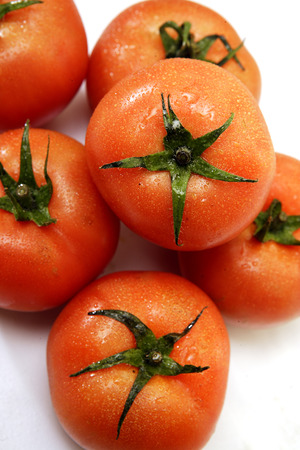 A closeup of a bunch of fresh red tomatoes with green stalks and water condensation  Фото со стока